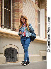 Full length young woman walking in city looking at mobile phone