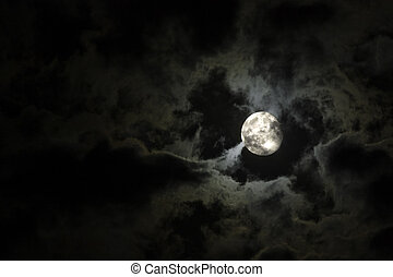 Full moon close-up and eerie white clouds against a black night sky
