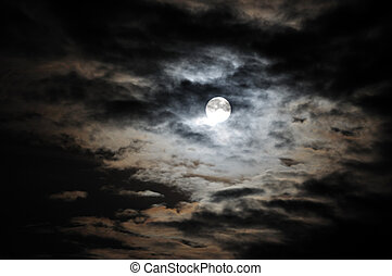 Full moon and white clouds on black night sky.
