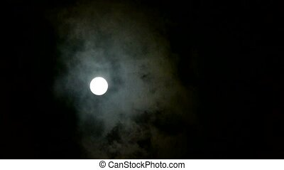 Full moon at cloudy sky, night flight over clouds.