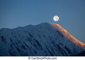 Full moon during a sunrise on the background of snow-capped...