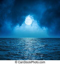 full moon in clouds over dark blue sea
