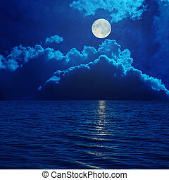 full moon in clouds over sea