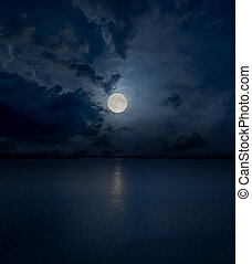 full moon in clouds over water