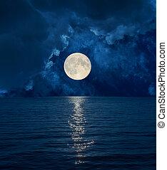 full moon in dark clouds over sea