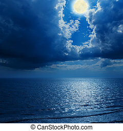 full moon in dramatic clouds and sea