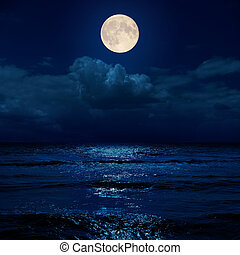 full moon in night over clouds and sea with reflections