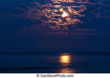 Full moon in night sky over moonlit water