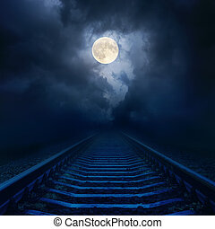 full moon in night sky with clouds over railroad