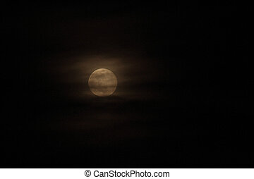 A full moon peeks out among wispy clouds in a pitch black sky