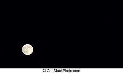 Full moon moves across the sky.