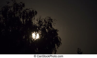 Full Moon Moves in the Night Sky through Dark Clouds and...