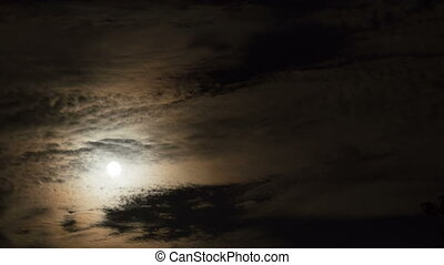 Full Moon Moves through the Clouds in the Night Sky....