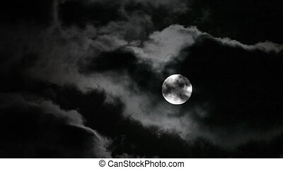 Full moon moving in and out clouds