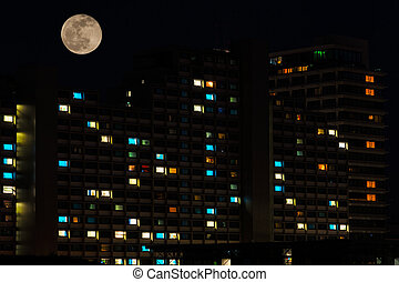 Full moon over colorful windows of residential house - Full...