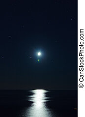 Full moon over dark water with reflections on it. The...