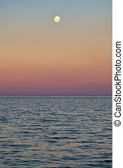 Full moon over sea and sunset with magenta tones