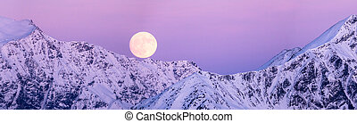 full moon rise over gorgeous winter mountain landscape