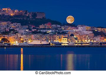 Full moon rises over coast of seaside city