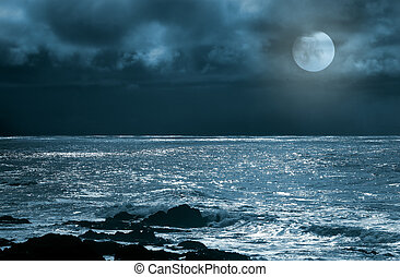 Rising full moon over sea and rocks in a cloudy night