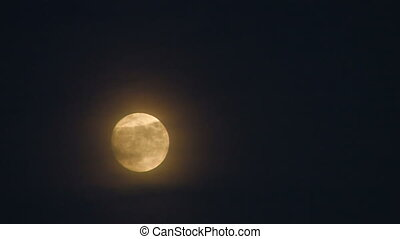 Full moon with clouds on dark sky,