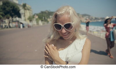 Full of emotions blonde in sunglasses walking on the French...