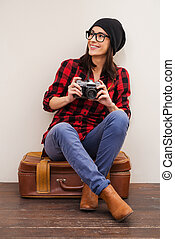 Full of inspiration.  Beautiful young woman in headwear holding camera and looking away while sitting on suitcase