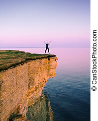 full of joy - happy man jumping on a cliff