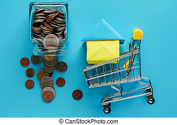 Full of money and coin in the glass jar with shopping cart and house model on blue background