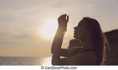 Full of thoughts woman with flowing hair wearing a dress standing by the sea at sunset on the rocky shore