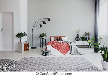 Full of trendy bedroom with comfortable king size bed, white wooden bed side table and plant, real photo with copy space on the empty wall