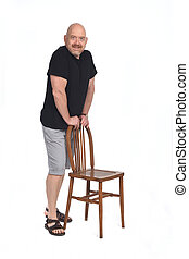 full portrait of a  bald man with shorts playing with a chair on white background,leaning  in the chair