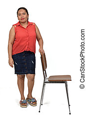 full portrait of a latinwoman with skirt  playing with a chair on white background