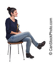 full portrait of a woman sitting on a chair cross-legged and looking to the side on white background