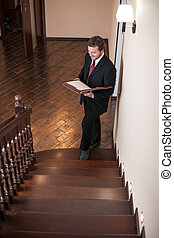 full portrait of confident male estate agent smiling. agent standing on ladder inside house and looking at documents