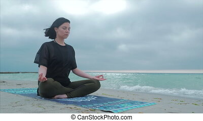 Close up view of hand - meditating in lotus position, cloudy weather and sea on the back ground. Young woman doing yoga poses cross-legged on beach at daytime. Happy young woman sunbathing and meditating in lotus padmasana pose