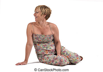full portrait of middle aged woman sitting on the ground on white