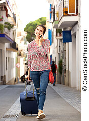 Full portrait of woman walking on city street with luggage and mobile phone