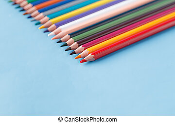 Full row of multycolor pencils on blue background