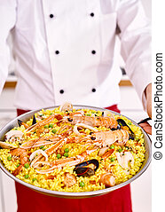 Full serving of pasta paella carried by chef - ...