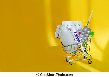 Full shopping cart medicines and pills in a on yellow background. Consumer buying panic about coronavirus covid-19 concept. First aid kit for home quarantine. Drug delivery.