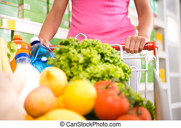 Full shopping cart - Woman at supermarket pushing a shopping...