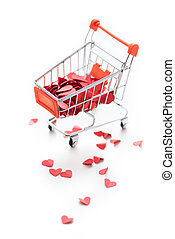 Full shopping trolley of red hearts isolated on white
