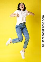 Full size of happy young asian woman jumping from joy, showing thumbs up in approval, posing over yellow background in jeans and casual white t-shirt