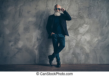 Full size photo of attractive harsh masculine man with eyewear eyeglasses standing near wall looking wearing coat jacket trousers shoes isolated over grey background