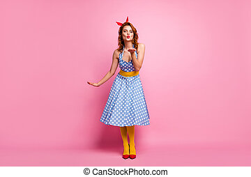 Full size photo of charming dreamy fancy girl send air kisses to rich wealthy guys wear red footwear polka-dot dress yellow pantyhose isolated over pink color background