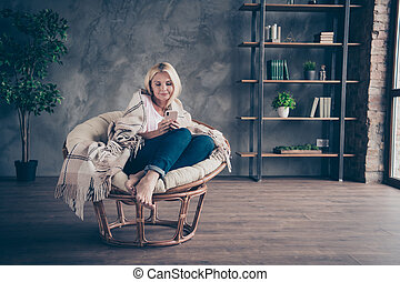 Full size photo of focused middle aged blonde hair woman use her cellphone read social media network enjoy autumn holidays sit on furniture white armchair covered with checkered blanket in living room indoors