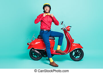 Full size photo of funky smiling handsome gentleman sit moped adjusting bow tie isolated on teal color background