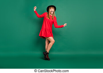 Full size photo of young beautiful happy excited crazy girl in red dress and black hat isolated on green color background