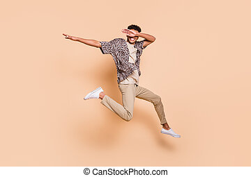 Full size portrait of crazy cheerful dark skin man arms dabbing have fun isolated on beige color background